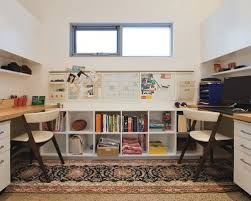 Trendy built-in desk home office photo in Sydney with white walls