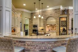 Cream traditional kitchen with brick breakfast bar and brick accent wall
