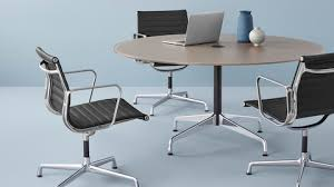 a round eames table surrounded by three eames aluminum group chairs select to go to