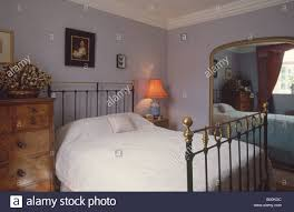 Mauve Bedroom Antique Brass Bed And Victorian Gilt Mirror In Mauve Bedroom Stock