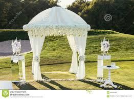 day orchid decor: white wedding arch with flowers and candle decoration on sunny royalty free stock images