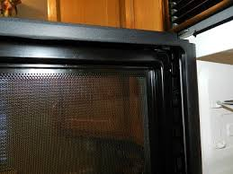 cleaning between the mesh screen and glass door on microwave