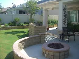 in demand rounded shaped stone concrete fire pit ideas as well as white wooden pergola as decorate rustic backyard landscape designs