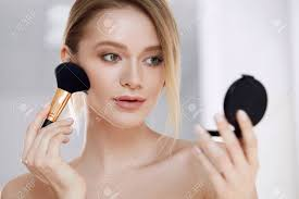 closeup of beautiful with fresh skin natural makeup applying powder foundation on face skin