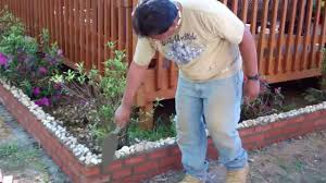 constructing a brick border around our back deck flower garden