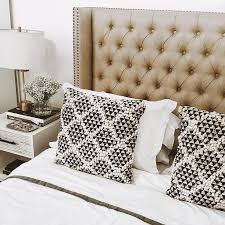 a gorgeous taupe leather headboard featuring diamond tufting and brass nailhead trim is a beautiful template for white bedding with black and white