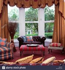 Living Room With Chesterfield Sofa Brown Leather Chesterfield Sofa In Bay Window With Swagged Tailed