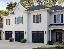 a large white brick house has three garages across the facade each painted black