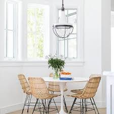 round saarinen dining table with modern wicker dining chairs