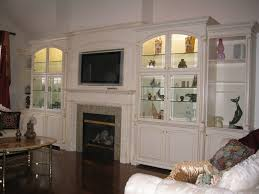 tv over fireplace featured quarter turned carved columns on wall units featuring gold glazing on