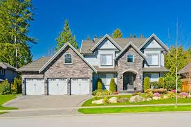 large house with grey stone facade and white garage doors 3 car outlines