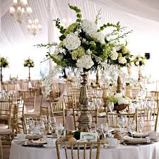 Gold, antique-style vases held white orchids mixed with green and white  hydrangeas. tablescape or centerpiece