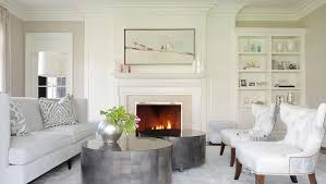 features a light gray sofa lined with gray animal print pillows facing a pair of white wingback chairs across from a pair of round metal coffee tables