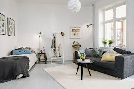 Small Bed also White Chandelier plus Gray Sofa and Coffee Table