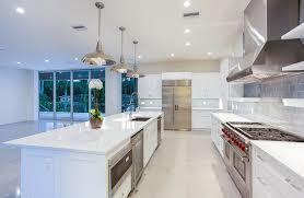 white cabinet kitchen with white quartz and gray glass subway tile backsplash
