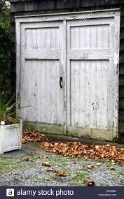 weather beaten old garage doors sloppily painted around the window panes