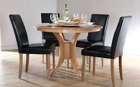 small wooden dining table set round with four black leather chairs glass