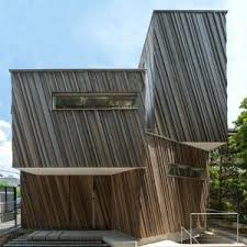 Kyodo House by Sandwich has wood facade and indoor swing
