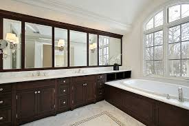 white bathroom cabinets with dark countertops. white bathroom with dark wood vanity running length of the room, matching bath surround cabinets countertops o