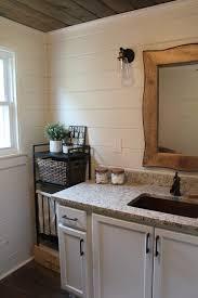 a modern farmhouse bathroom with a copper tub copper sink wood plank ceiling