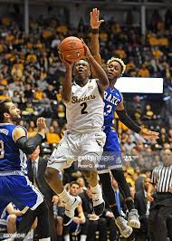 Guard Dishon Smith of the Wichita State Shockers drives in for a ...