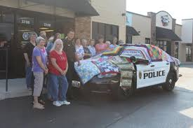 Handmade Quilts Help Comfort Kids | KSMU Radio & Members of Community Quilts by a Squad Car Covered with their Creations.  Michele Skalicky. A Quilt is Created by Ozark Piecemakers Quilt Guild Adamdwight.com