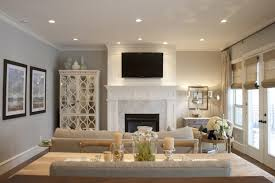 modern living room style with living room recessed lighting design and light gray fabric sofa and round corner table facing small fireplace also mirrored