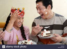 Father And Daughter Eating Birthday Cake With Cake On Their Faces