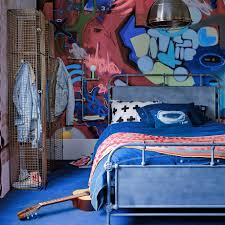 Blue teenage boy's room with graffiti wall, metal bed and guitar