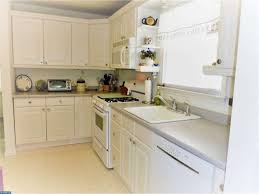 open eat in kitchen with updated custom kitchen cabinets with plenty of storage built in microwave with exhaust
