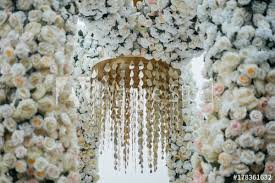 golden chandelier hahngs on the flower arch of white and pink flowers