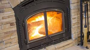 wood burning fireplace with a stone surround and metal fireplace insert
