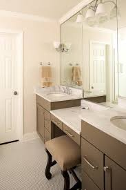 white and taupe bathroom boasts a taupe makeup vanity paired with a taupe linen stool flanked by taupe washstands topped with white marble with gray veining