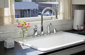 simple printed curtain and white drop in sink with chrome finished faucet for elegant kitchen plan