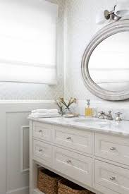 bathroom features gray shaker vanity: this calming white and gray bathroom features upper walls clad in gray trellis wallpaper and lower walls clad in wainscoting lined with a white freestanding