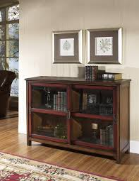 classic walnut brown bookcase with red sliding glass doors frame accent plus oval metal handle on brown laminated floor