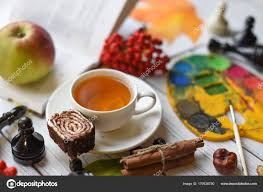 a cozy autumn photo with a cup of tea watercolors a drawing a book autumn leaves and cinnamon sticks photo by 5231342 gmail