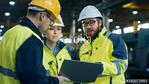 Three Industrial Engineers Talk With Factory Worker While Using
