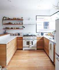 a kitchen of natural wood and white countertops and appliances looks very inviting
