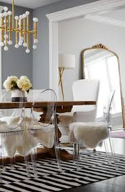 adorable acrylic dining chairs also zebra rug pattern also white fur chair cover huge antique mirror and artistic chandelier design also gray wall paint