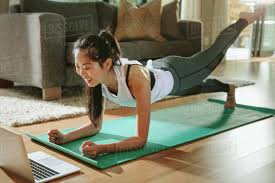 smiling woman exercising at home and watching training s on laptop chinese female doing planks with a leg outstretched and looking at laptop