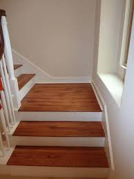 ... Laminate Flooring In A Wood Pattern Against White Banisters Creates A  Classic Look Wood Stairs Pricing ...
