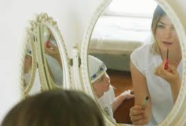 sad child looking in mirror. daughter watching mother put on makeup sad child looking in mirror