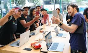 iphone japan. a shop employee briefs customers on the new features of iphone 8 handset at an iphone japan