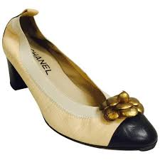 chanel black and tan pumps with antique gold tone camellia ornaments for