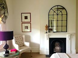 cool and unique shaped mirror over the fireplace a white corner armchair round table with glass