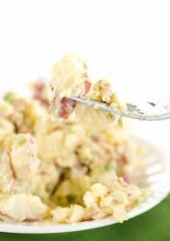 a close up shot of potato salad on a fork with a plate of potato