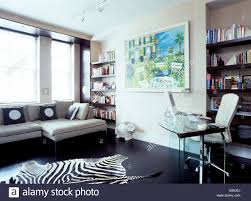 office rug. Faux Zebra Skin Rug On Black Flooring In Modern Home Office With Laptop Computer Glass Table