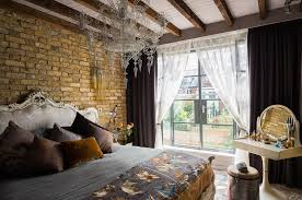 neo baroque bedroom with brick wall and chandelier