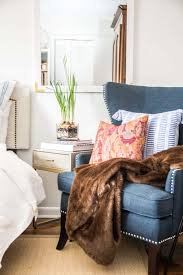 i filled the chair with a brown faux fur throw seriously the best faux i ve ever felt and a cozy ikat pillow to add the perfect pop of red to the